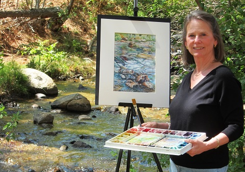 Lynn Marit Peterson, having finished painting one of her scenic watercolors